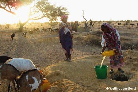 Mädchen schöpft Wasser an einer Wasserstelle
